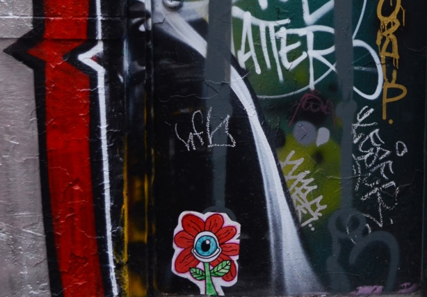 small sticker of a daisy with red petals and an eye in the center, on a wall already covered with painted street art