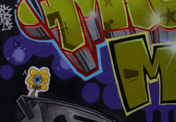 small sticker of a daisy with yellow petals and an eye in the center, on a wall already covered with painted street art