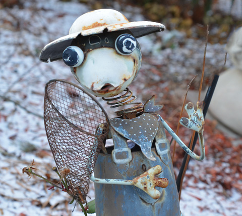 little metal character made of found objects and rusty metal, hat, fishing net, overalls,