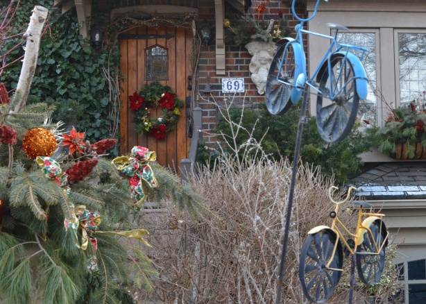 yeard decorations of two small metal bikes, one blue and one yellow, in front of a house with Christmas wreath on the door and other Christmas greenery decorations too