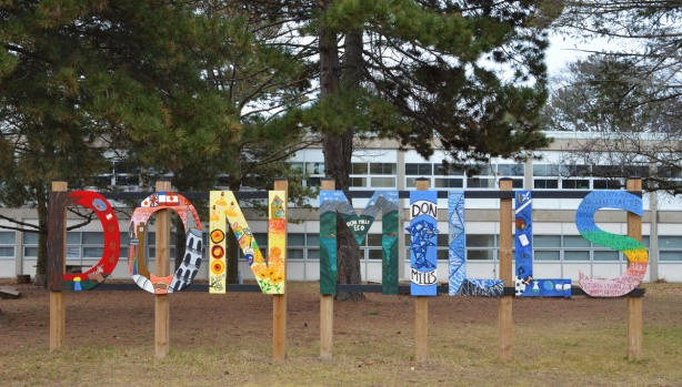 Painted sign tht says Don Mills, in front of Don Mills Sceondary school. Each letter is a different colour with decorations on them (pictures) painted by students