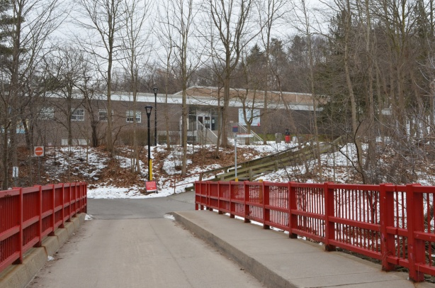 single lane bridge with wide sidewalk and bright red metal barricades on side, brick building in the background, trees, winter,