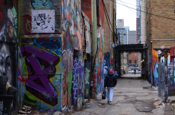 a man walks down graffiti alley