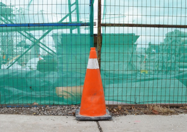 orange construction cone beside a fence with a green construction cloth covering over it