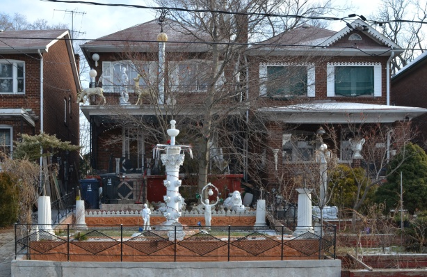 two adjacent two storey houses with lots of white statues and fountains in the front yards
