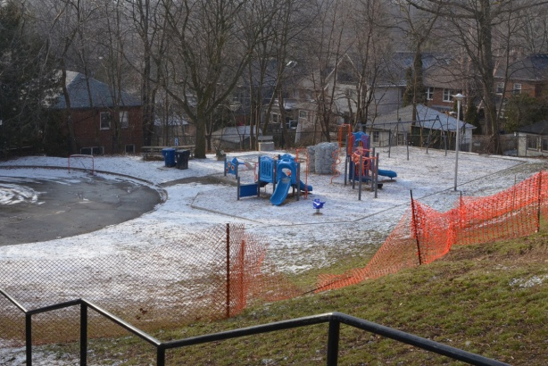 looking down a hill towards a park with a playground, backyards and houses beyond that. orange snow fence, railings of the stairs going down the hill