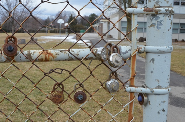 a few locks, rusted, on the chainlink fence around Don Mills Secondary school, playing fields and basketball hoops in the background
