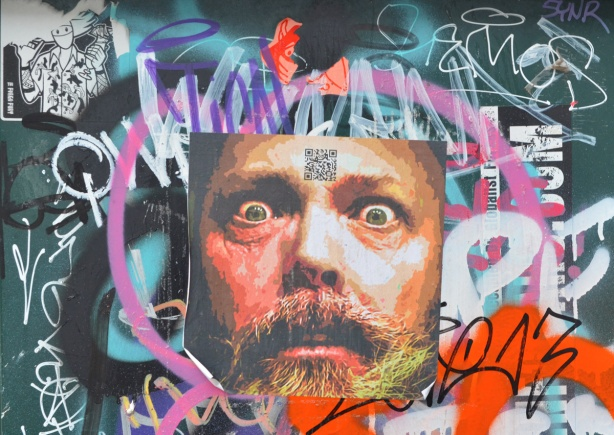 pasteup of a photo of a man's face, with beard and moustache, other scribbles around the face