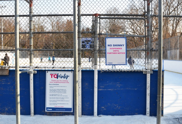 outdoor skating rink at Rennie Park, winter, with two signs regrding the rules for outdoor rinks during covid times, a few people are skating