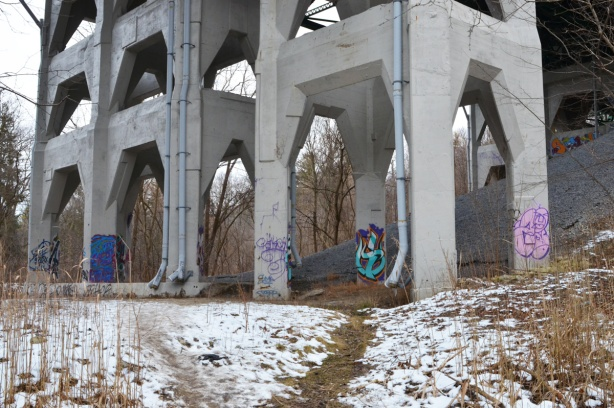 concrete pillars with some graffit on them, holding up a bridge, over snowy ground