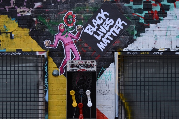 black lives matter words on a wall with an urban ninja squadron t bonez in a pink suit and holding a red daisy with one eye in the center, graffiti alley