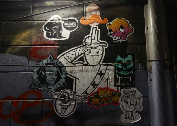 stickers and paste ups on a wall in graffiti alley