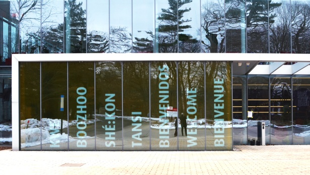 glass wall of newest Glendon college building, glass with the word welcome in different languages etched onto it, reflections in the glass