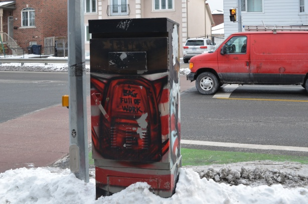 traffic box on sidewalk painted as back of a person in a red and white striped shirt with a backpack on. outside of backpack are words bag full of work, Red van on road, and houses behind that, snow on the ground,