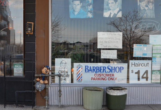 storefront on kingston Road in Cliffside, barber shop, closed because of covid, faded pictures of mens heads show casing hair styles in the window,