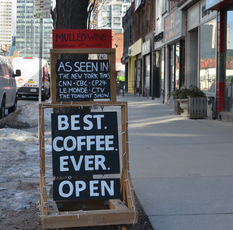 sign on sidewalk advertising a coffee shop that says best coffee ever also mulled wine