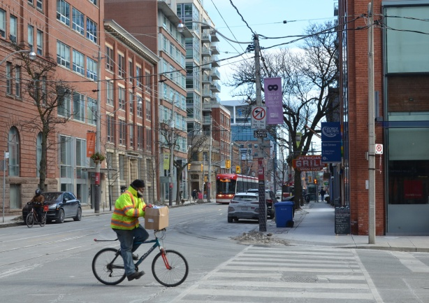 man making a delivery , a box, on a bike, KIng street,