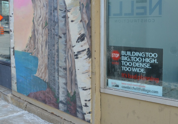 small mural of birch trees beside Scarborough bluffs, on outside wall beside a window with a protest sign in it. Poretesting redevelopment of parts of Kingston Road with buildings that are too big, too tall, too wide
