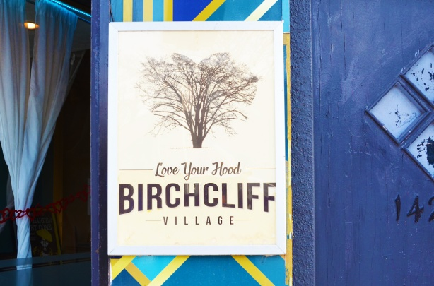 poster on the outside of a store, blue wall, picture of a tree and words that say Love your hood, Birchcliff village