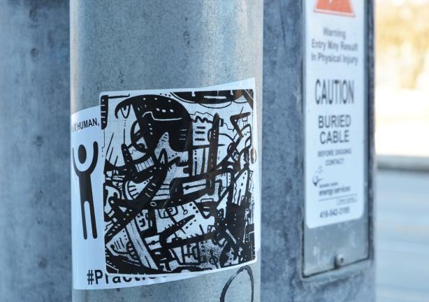 black and white sticker graffiti on a pole