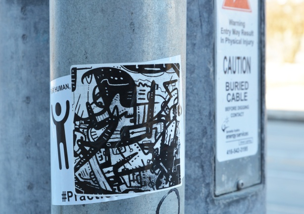 black and white sticker graffiti on a pole