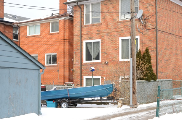 small blue boat on a trailer parked by garage in an alley behind multiplex houses 3 storeys high, red brick.