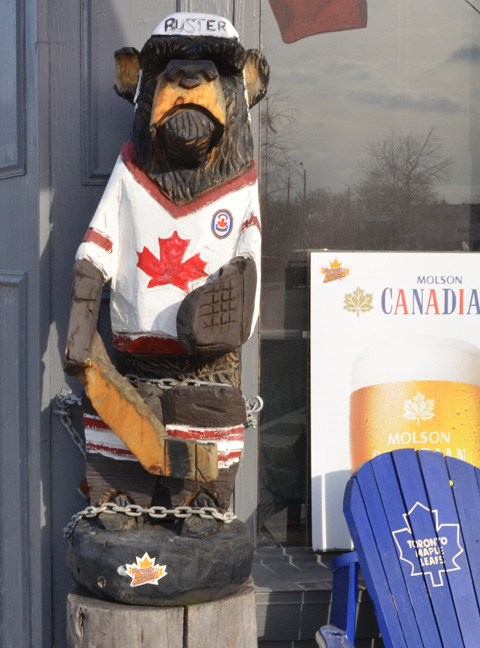 carved wooden bear, Buster, with Canada flag hockey shirt on, holding a hockey stick,