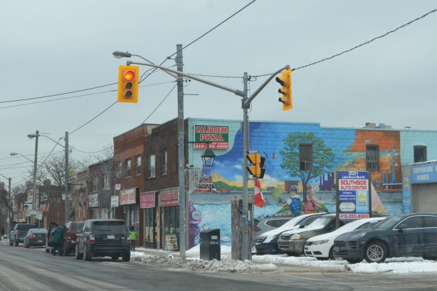 mural on the side of a two storey brick store on Lakeshore in Mimico, sign says Calibreze Pizza.