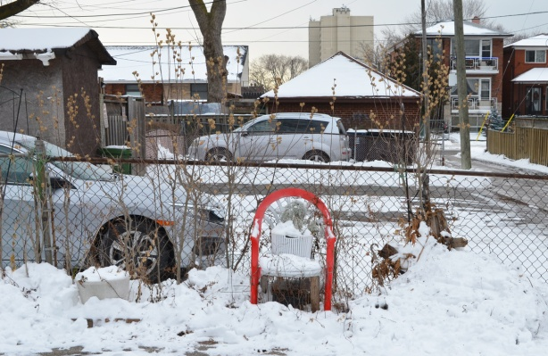 a chair in the driveway by an alley, in the snow, cars, chainlink fence behind the chair.