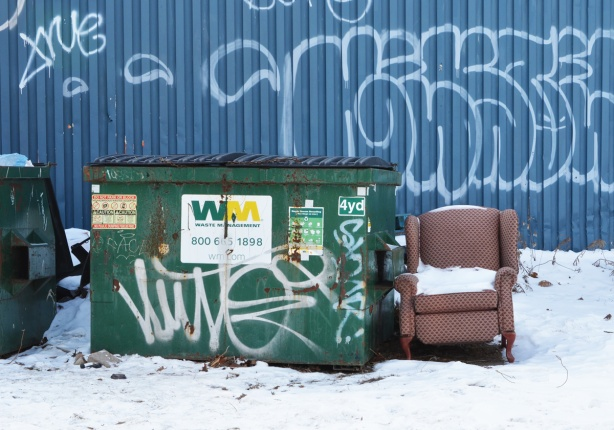 an old beige arm chair, with snow it, outside beside industrial garbage bins