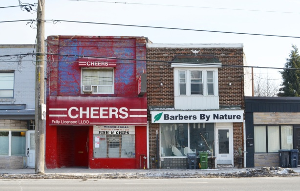 three old two storey brick storefronts, one is Cheers restaurant painted bright red, the other is Barbers by Nature