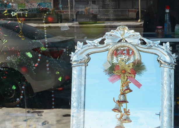 looking in the window of a store, a mirror with an ornate silver colour frame, Christmas bells attached to it with ribbons and greenery