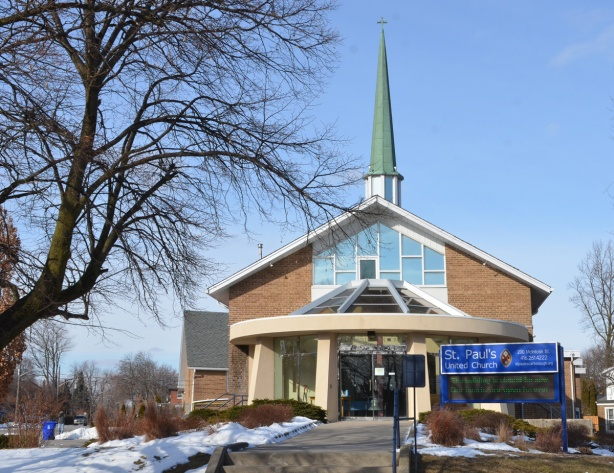 front of St. Pauls United Church in Cliffside Scarborough, narrow green steeple, round glass entranceway, stairs leading from the sidewalk to the church