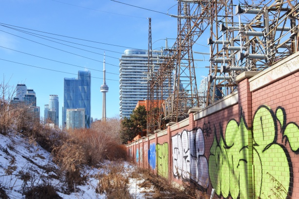 graffiti on the wall around the hydro substation, lots electrical stuff, with CN Tower and downtown buildings in the background