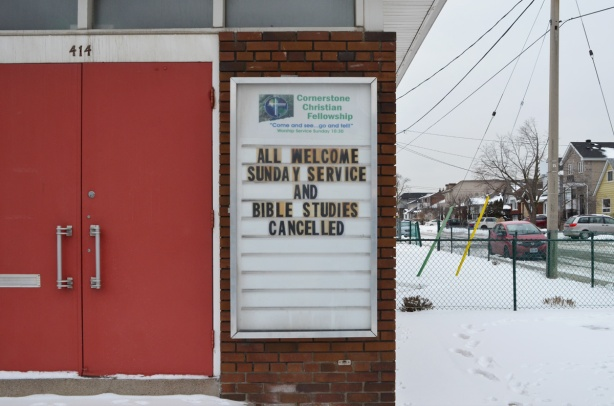 sign beside the red doors of Crossroads Christian fellowship church that says All welcome Sunday service and bible studies cancelled