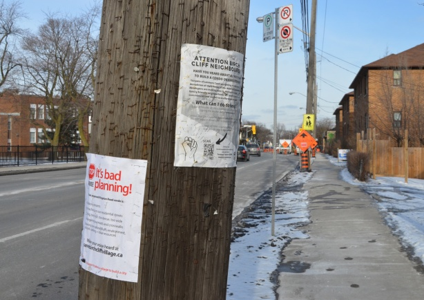two posters on a wood utility pole, protesting redevelopments in the neighbourhood