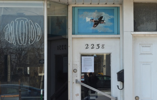 entrance to a store 2258, with a painting of an old airplane over the door