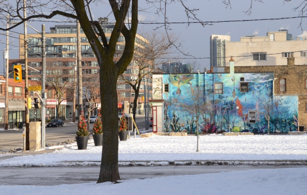 picture of a mural as seen from across a park, street scene as well. snow, winter,