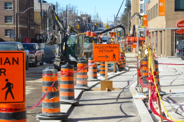 Eglinton Ave west sidewalk through Crosstown construction, lots of orange and black cones, pedestrian detour signs