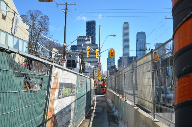 Eglinton Ave west sidewalk through Crosstown construction, barriers on both sides, narrow, tall buildings at Yonge and Eglinton in the background