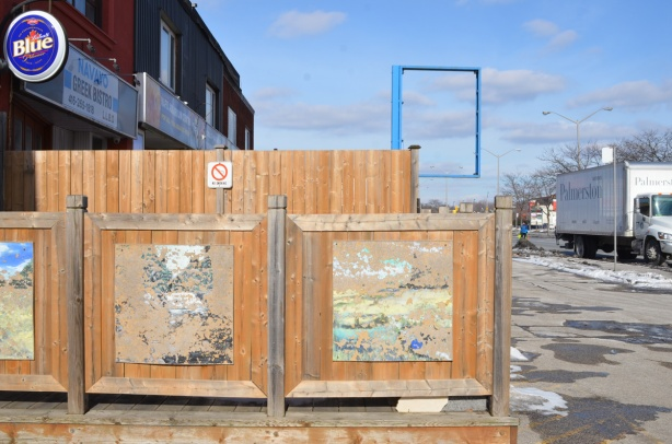 wooden fence around a patio, with two old paintings that are faded and peeled so you can't tell what they were pictures of, in the background, an empty blue metal frame that once held a sign for a store
