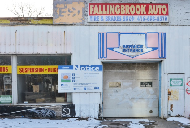 side entrance and car door of Fallingbrook garage, mechanic, service entrance, now with a development notice sign on it
