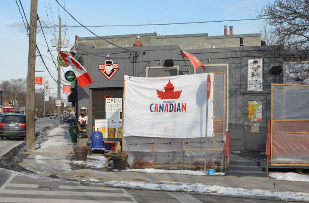 Molson Canadian flag outside a bar, also muskoka chairs and a carved wood bear, a Canadian flag too.