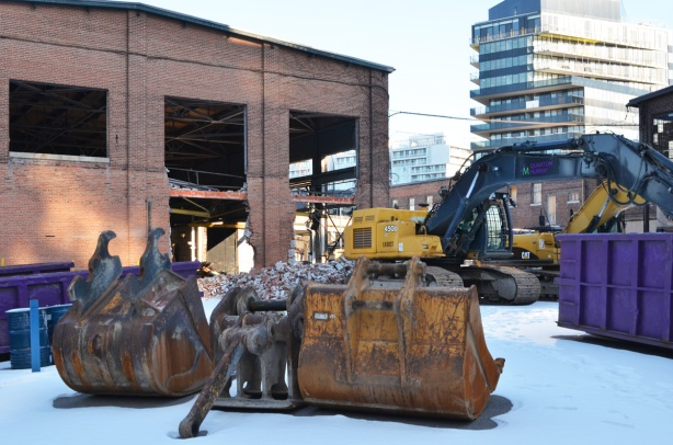 machinery in front of old foundry building that demolition was started on, and then stopped