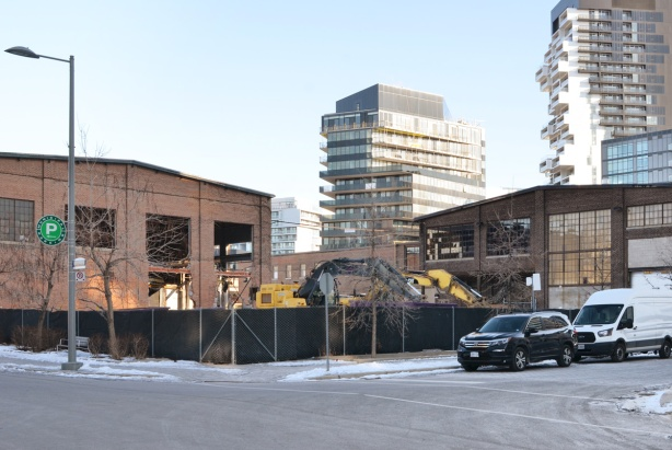 old foundry building behind hoardings, new condo in the background