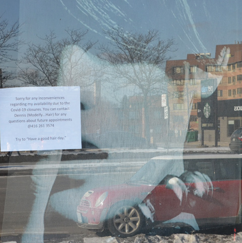 looking in a store window, a large picture of a woman looking back out, with a sign on the window re opeings and closings for covid 19