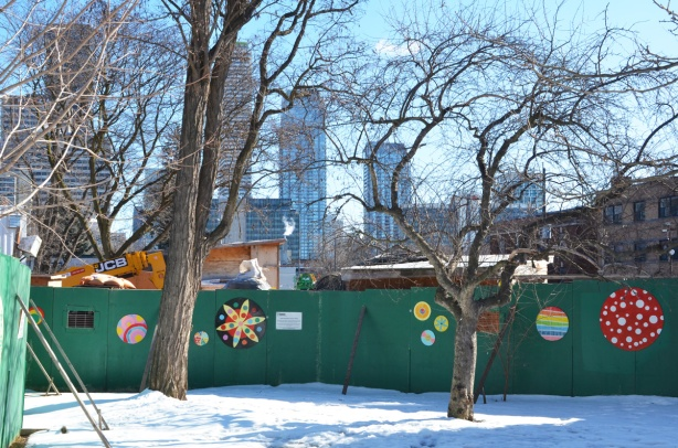 green plywood hoardings around Crosstown construction, with artwork on them, painted designs on wood