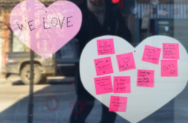pink post it notes with words, beside big pink heart, in the window of a store, notes all say what people love
