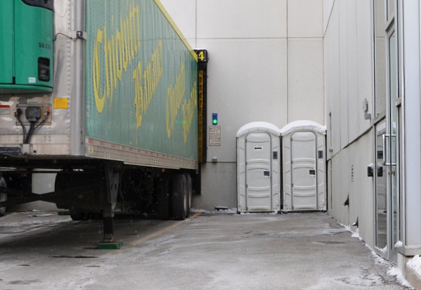 two white port a potties beside a parked truck container back part