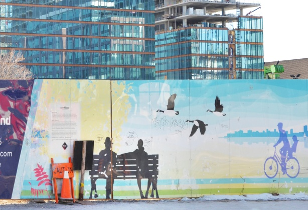 painted hoardings of a couple sitting on a bench, a child on a bike, some Canada geese, by Pam , around a construction site